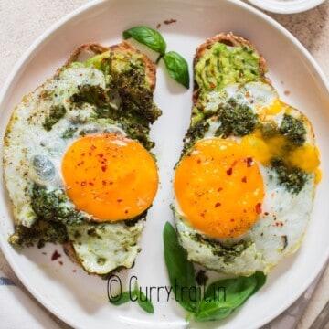two avocado toast with pesto eggs on it