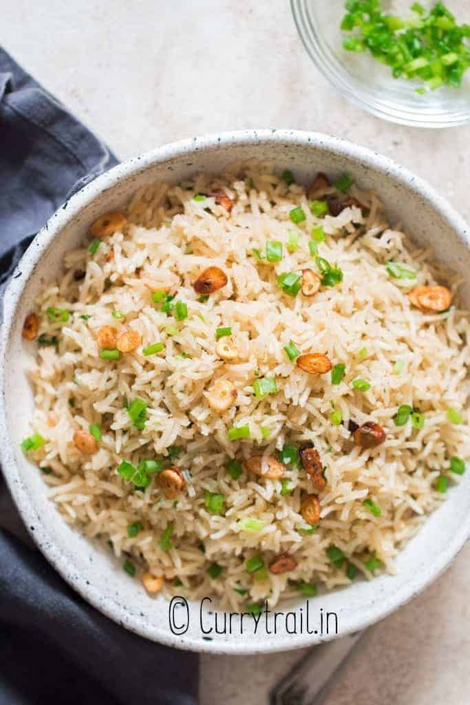 garlic fried rice with crispy garlic chips and scallions as garnish on top