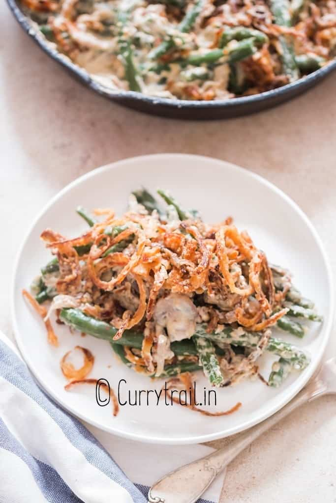 green beans cooked in creamy gravy served in plate with crispy onions on top