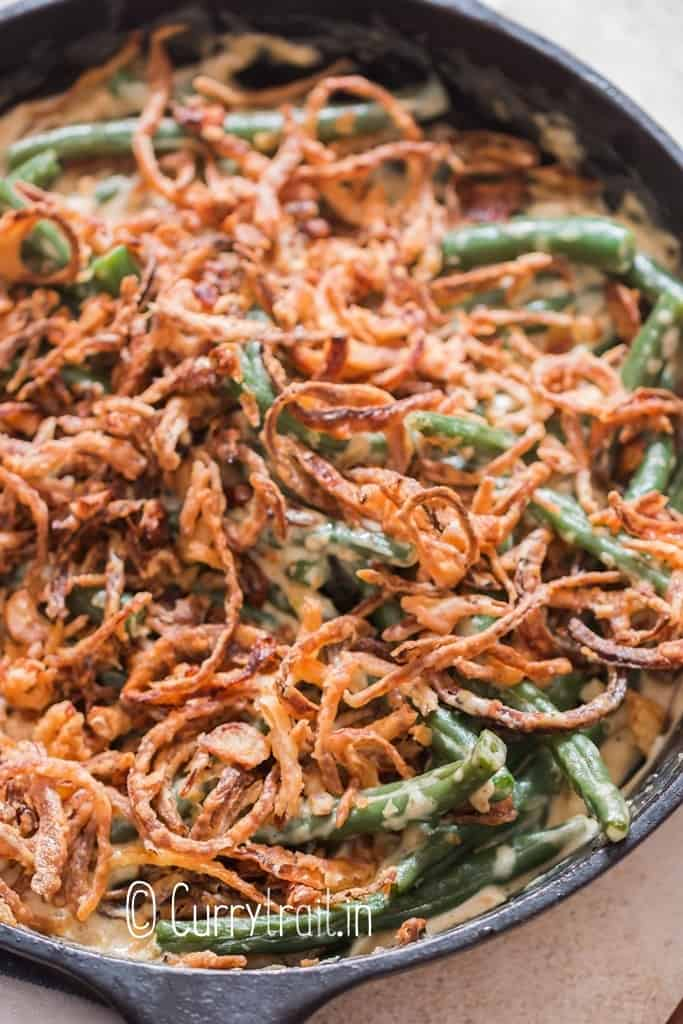 close up view of green beans cooked in creamy gravy with crispy onions on top